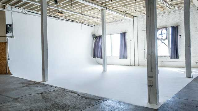 seamless white cyclorama cycwall for film photography production in modern industrial warehouse with white brick texture and pillars