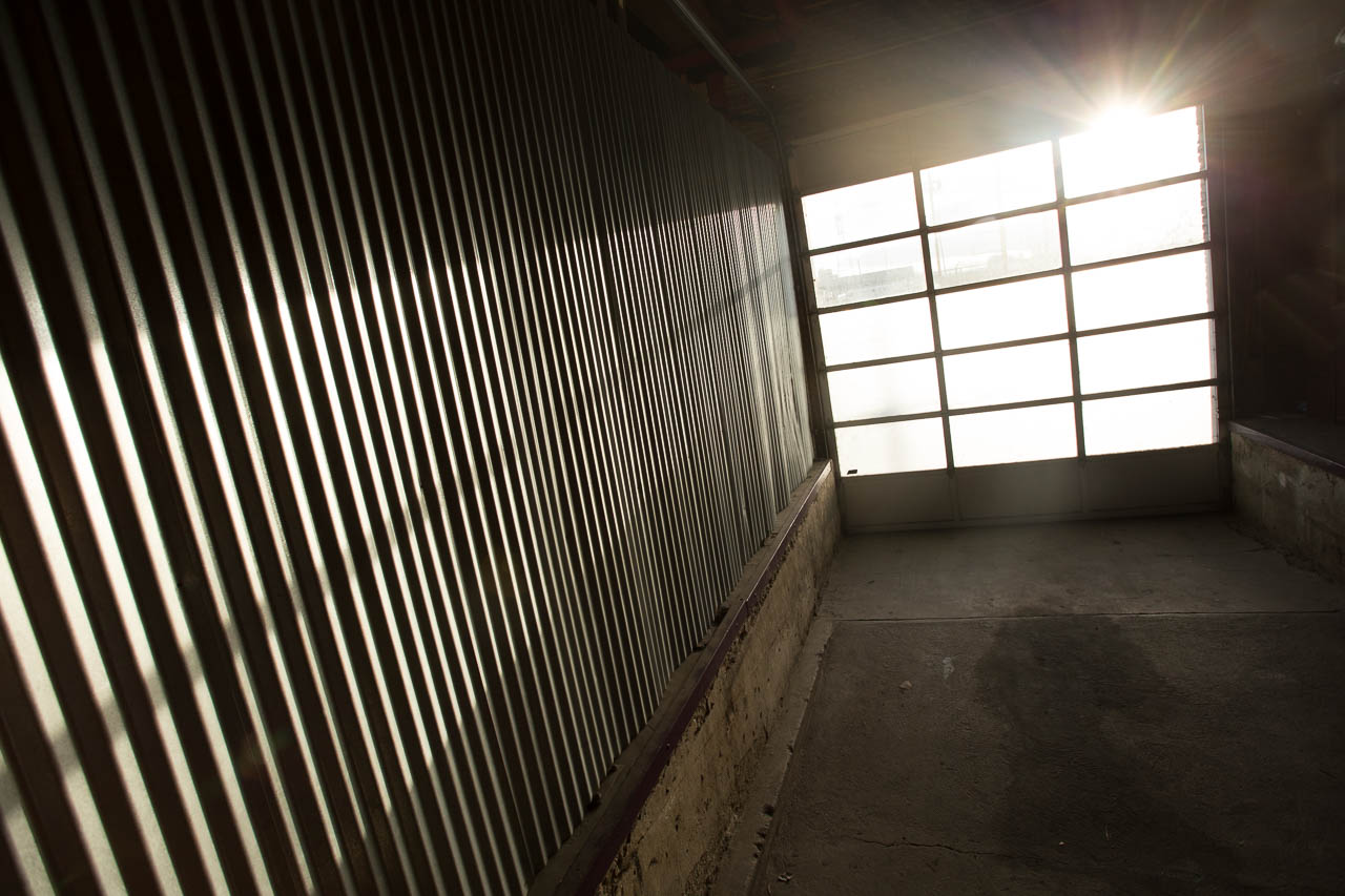 industrial warehouse loading dock with corrogated metal roll up door windows and concrete floors located in downtown los angeles