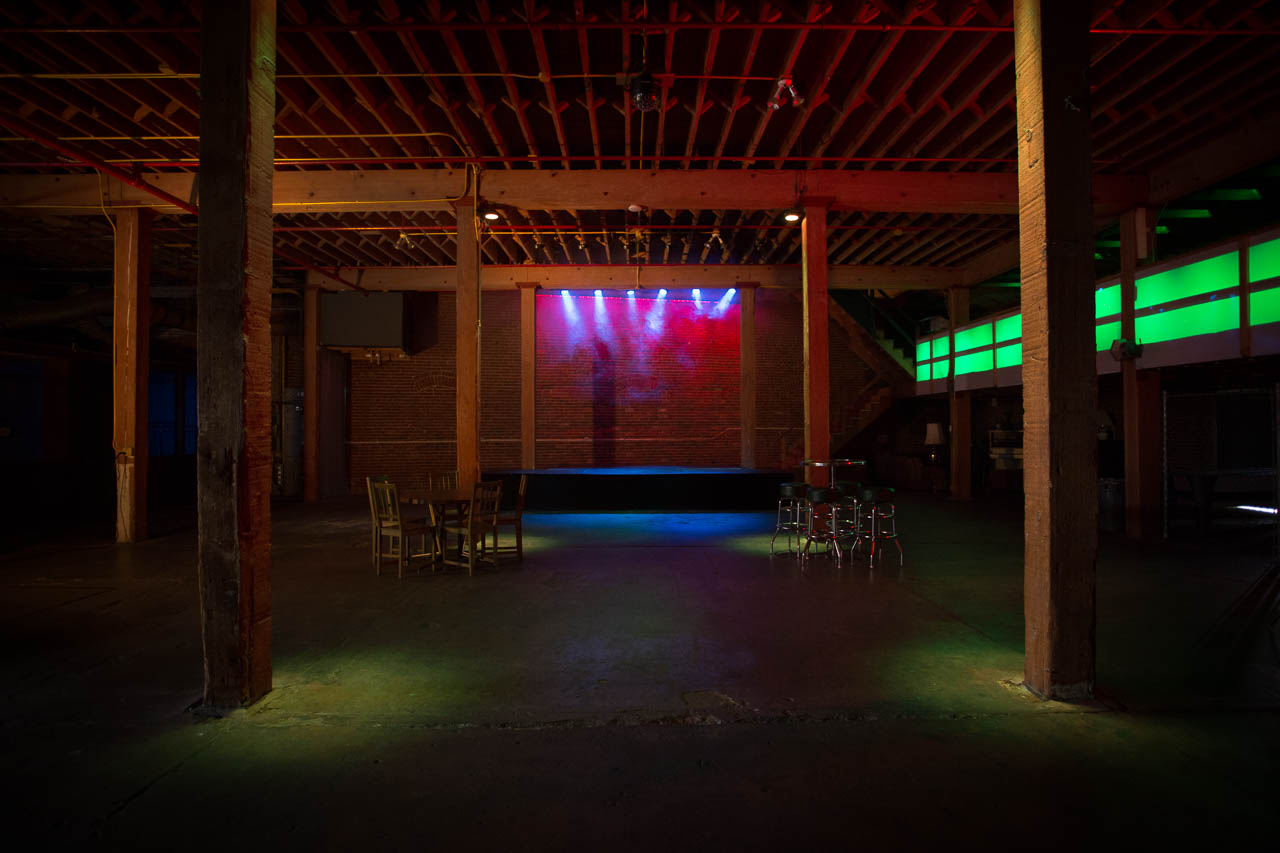 large underground warehouse night club with stage brick wall pillars rafters and led lighting for film and photo production