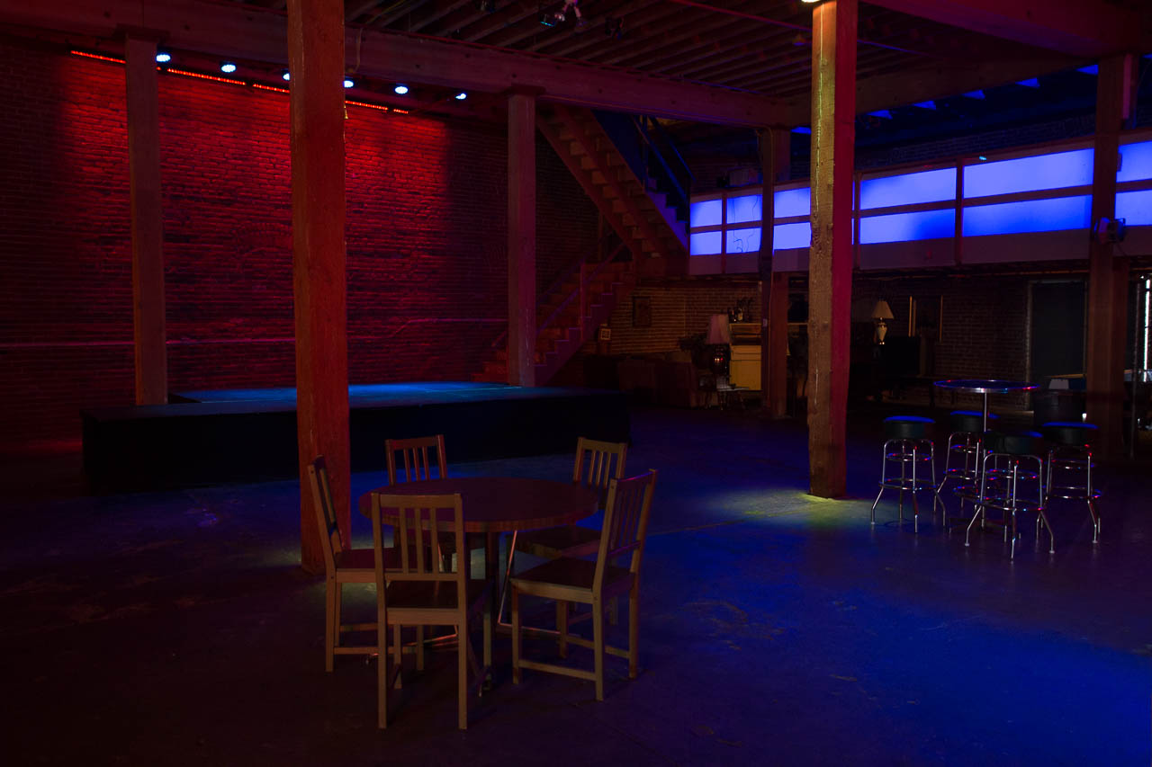 large underground warehouse night club with stage brick wall and led lighting for film and photo production