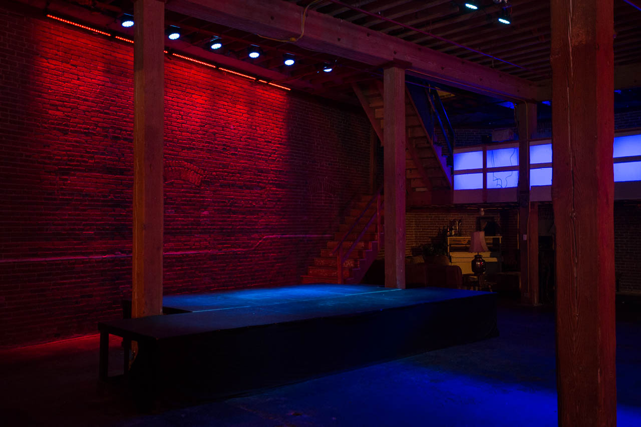 underground warehouse night club with stage brick wall and led lighting for film and photo production