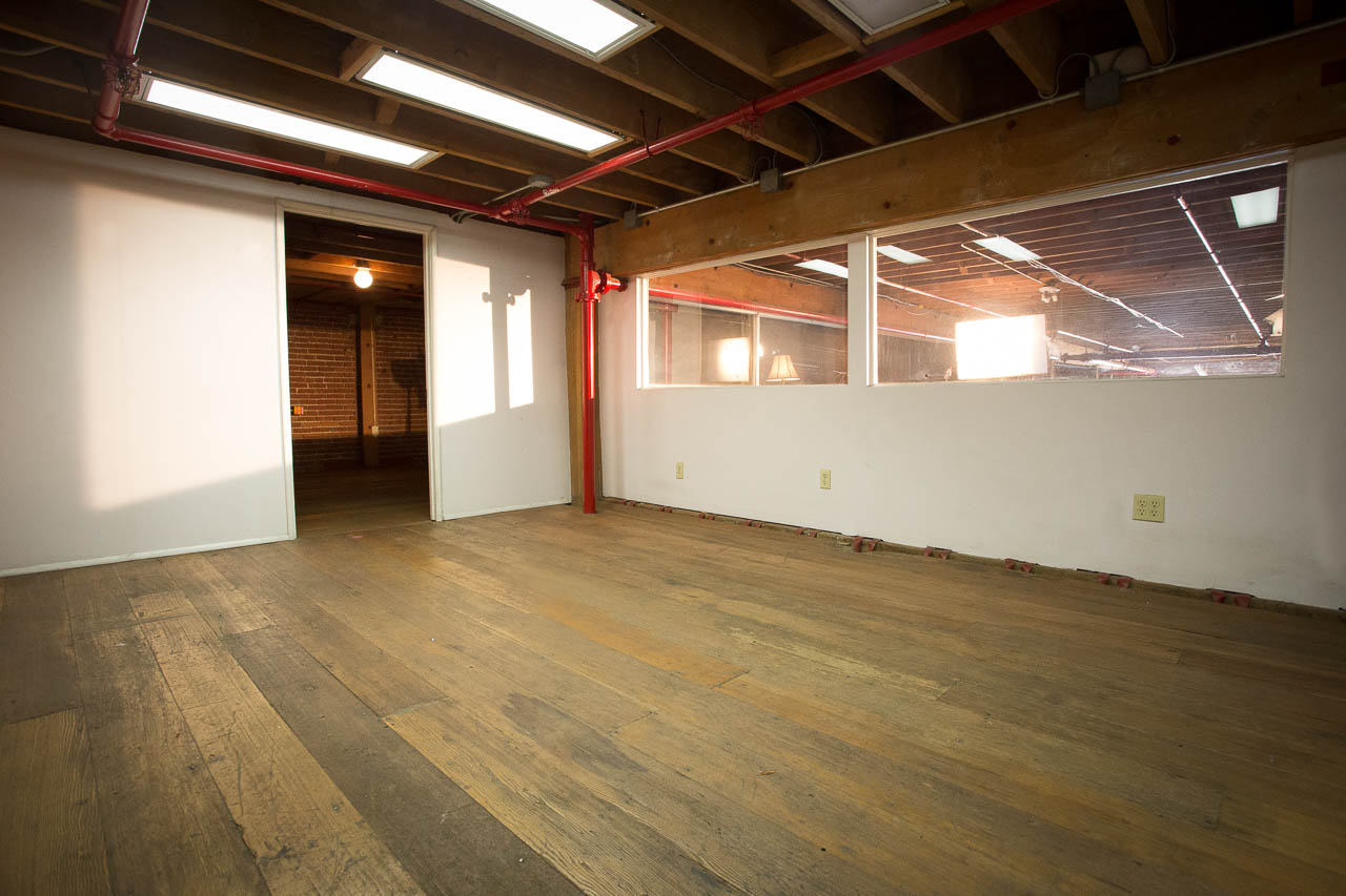 industrial wood flooring rafters brick walls and white walls in downtown los angeles film studio for film and photography shoots