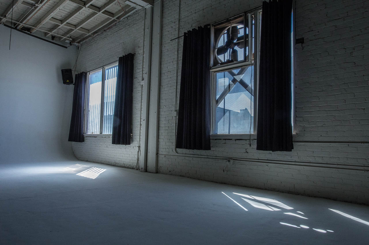 white cyc wall with industrial fans and natural light in downtown los angeles film and photo production warehouse