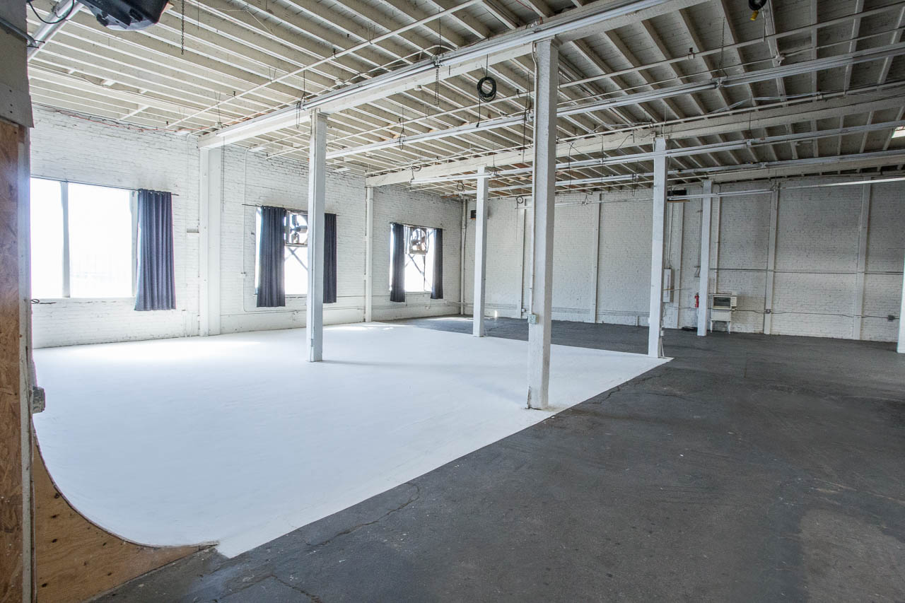white seamless backdrop with open space and natural sun light in industrial warehouse for film and photography production projects