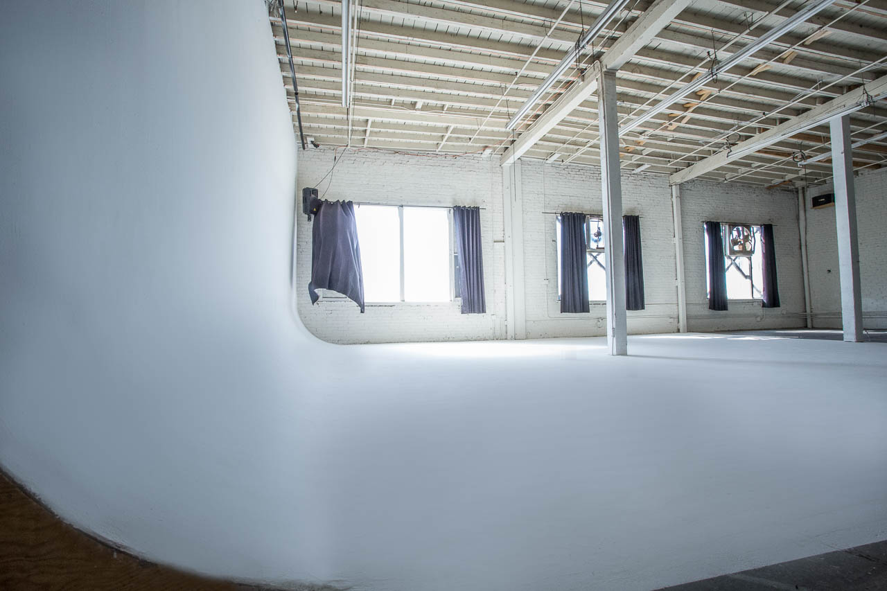white industrial seamelss white backdrop cyclorama cycwall shoot space LA with window fans for gritty warehouse feel in dtla