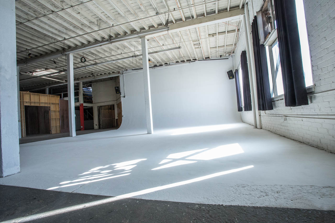 industrial painted white seamless backdrop cyclorama cycwall with rafters pillars and natural light window fans for rent in downtown los angeles
