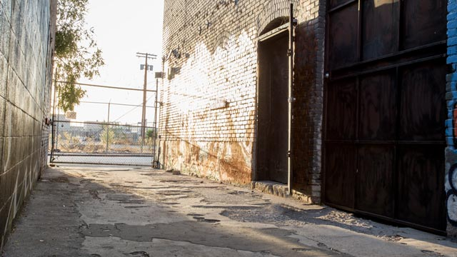 gritty back alleyway with gated street access and heavy metal doorway leading to la warehouse space for film and photo production in los angeles